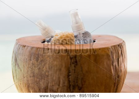 skin care, body care, summer and health concept - bowl with moisturizing spray and wisp at hotel beach or spa