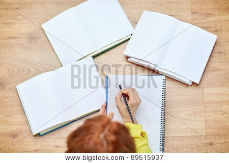 people and education concept - close up of female hands writing to notebook at school