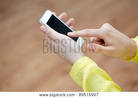 people, technology and internet concept - close up of teenage girl hands with smartphone at home