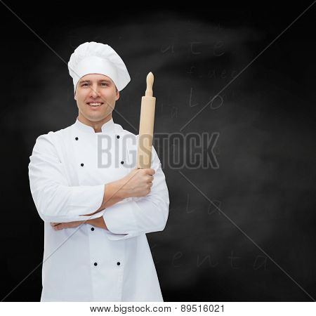 cooking, profession and people concept - happy male chef cook holding rolling pin over black chalk board background