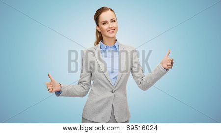 business, education, gesture and people concept - smiling businesswoman showing thumbs up over blue background