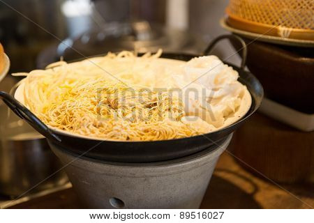 cooking, kitchen and food concept - bowl of rice noodles garnish at asian restaurant