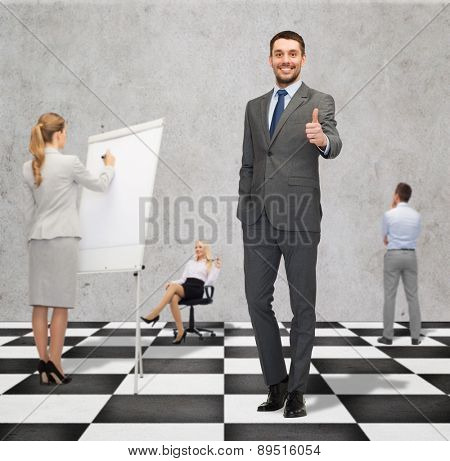 business, people, success, teamwork and strategy concept - smiling young businessman showing thumbs up gesture standing on checkerboard pattern floor over gray background and businesspeople