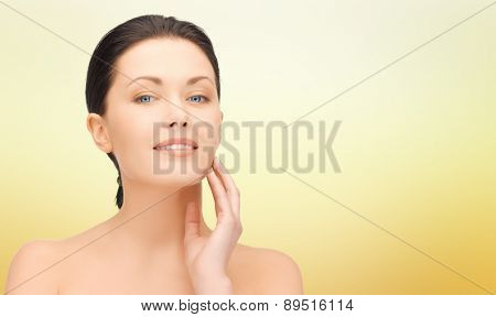 beauty, people and health concept - beautiful young woman touching her face over yellow background