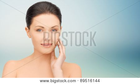 beauty, people and health concept - beautiful young woman touching her face over blue background