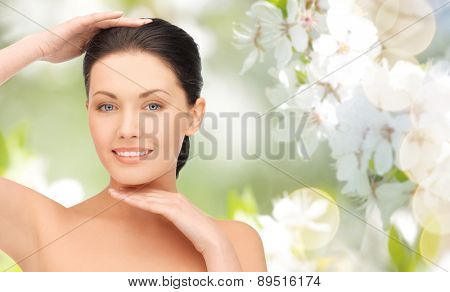 beauty, people and health concept - beautiful young woman touching her face and chin over green blooming garden background