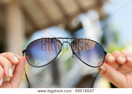travel, tourism, summer vacation, beach and fashion accessories concept - close up of woman hands holding shades or sunglasses with parasol reflection