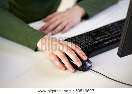 school, people, technology and education concept - close up of male student hands holding computer mouse at table