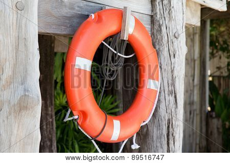 summer, beach, swimming and life saving concept - lifebuoy or life preserver hanging on rescue booth