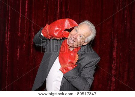 A Business Man is attacked by his own Lobster Claw Hands while in a Photo Booth.