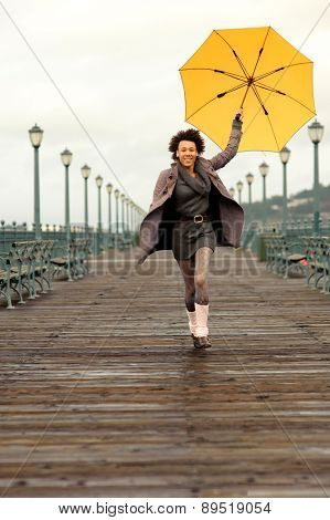 Outdoor photo of young african american woman walking on the pier.