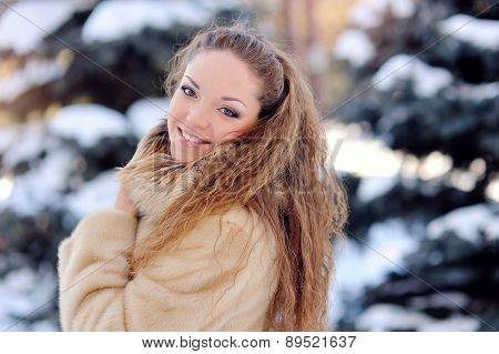 Beautiful Woman On The Street Near Fir-tree In Winter