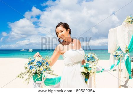 Wedding Ceremony On A Tropical Beach In Blue. Happy Bride Under The Wedding Arch