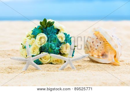 Two Wedding Rings With Two Starfish, Wedding Bouquet And A Large Shell On A Sandy Tropical Beach.