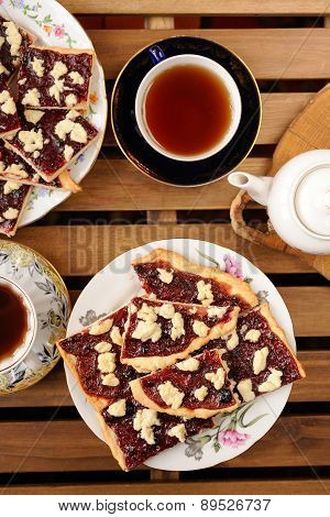 Berry Jam Cookies In White Plate, Two Cup Of Tea, White Teapot On Stripe Wooden Background Topview