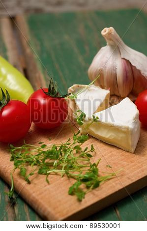 Two Slices Of Camembert And Vegetable On Chopping Board