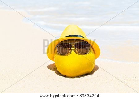 Funny Coconut In Sunglasses And Yellow Hat Lies On A Sandy Tropical Beach. Sea In The Background .