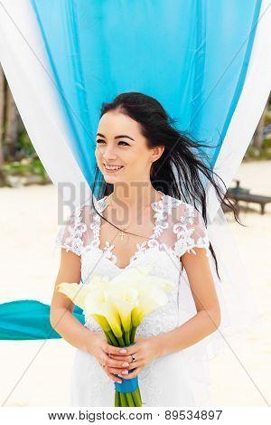 Wedding Ceremony On A Tropical Beach In Blue. Happy Bride Under The Wedding Arch