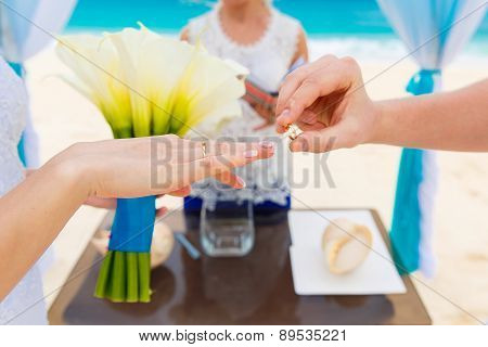 Groom Giving An Engagement Ring To His Bride Under The Arch Decorated With Flowers