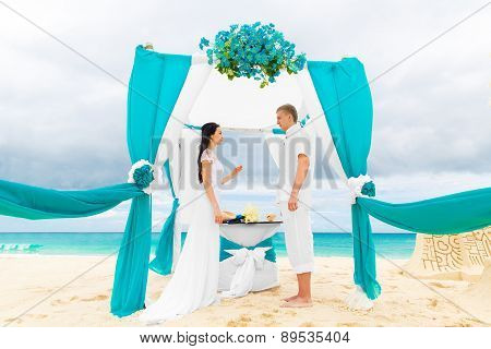 Bride Giving An Engagement Ring To Her Groom Under The Arch Decorated With Flowers