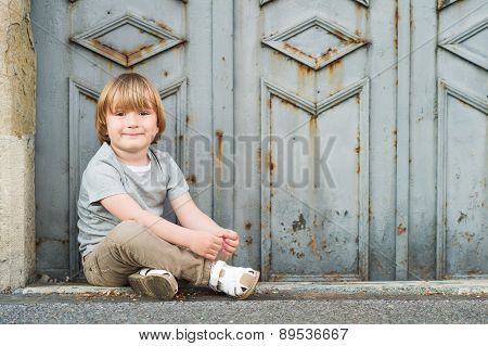 Outdoor portrait of a cute little blond boy of 4 years old