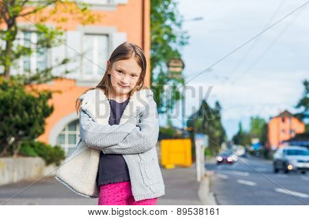 Outdoor portrait of a cute little girl in a city