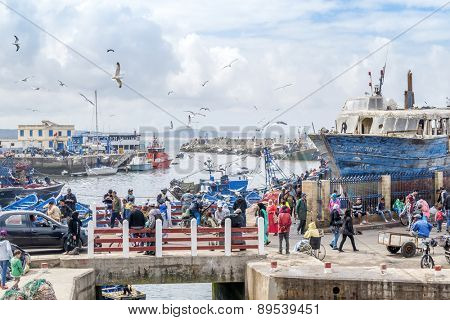 AS-SAWIRA, MOROCCO, APRIL 7, 2015: Local people and tourists walk in fishing port of As-Sawira