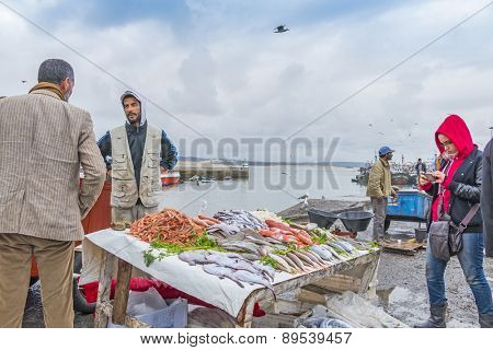 AS-SAWIRA, MOROCCO, APRIL 7, 2015:  Fishermen sell fish and seafood in port of As-Sawira while a tourist takes photos with her cellphone