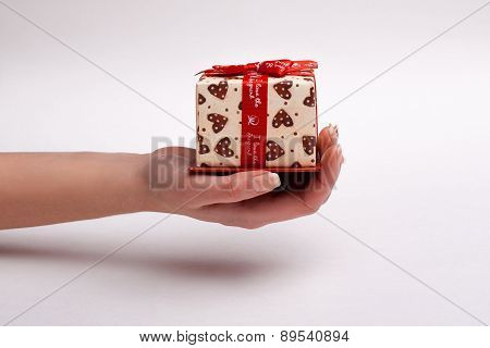 Woman's Hand Gives A Beautiful Gift Box With A Bow.