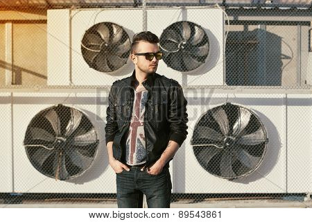 Portrait Of A Hipster Man In A Black Leather Jacket And Sunglasses. Stands Near Air Conditioners.