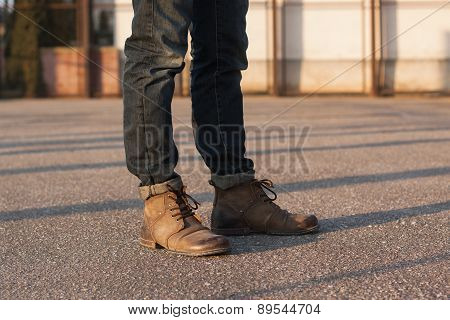 Men's Legs With Jeans And Boots. Hipster At Sunset.