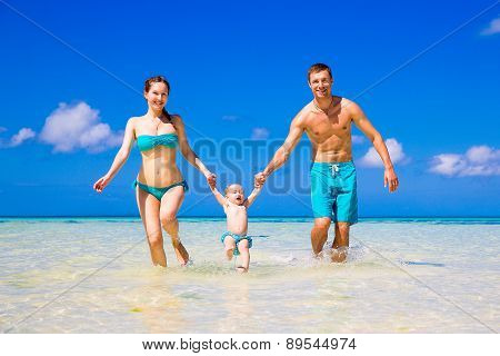 Happy Family, Mom, Dad And Little Child Having Fun On A Tropical Beach. Summer Vacation Concept.