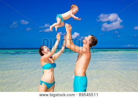 Happy Father Mother And Child Having Fun On A Tropical Beach. Summer Vacation Concept.