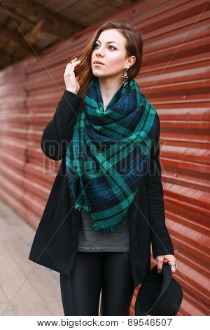 Portrait Of A Pretty Woman In A Coat With A Scarf. Standing Near A Red Metal Fence.