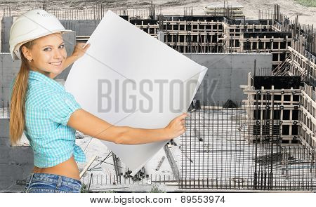 Smiling young woman in hard hat holding paper