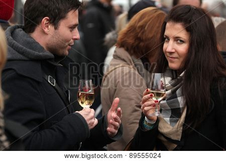 PRAGUE, CZECH REPUBLIC - NOVEMBER 11, 2012: Young couple tastes young wine during the celebration of Saint Martin Day in Prague, Czech Republic.