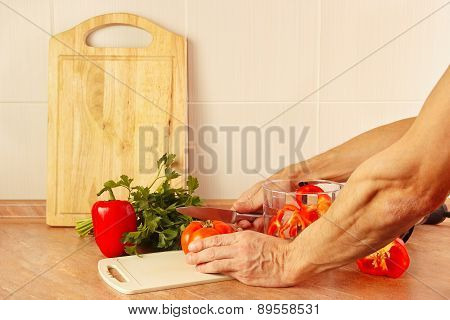 Hands cook cut red tomato on kitchen table