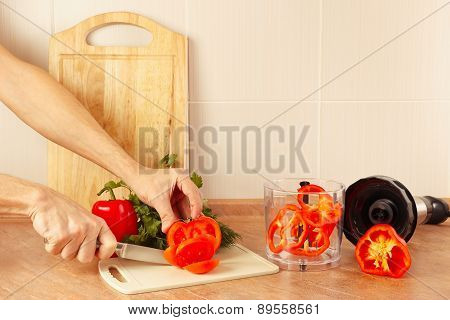 Hands chefs cut fresh tomato on kitchen table