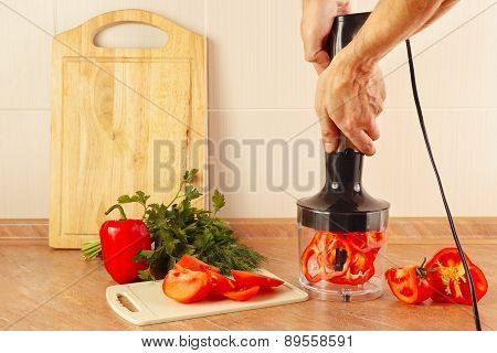Hands cook are going to shred red pepper in blender
