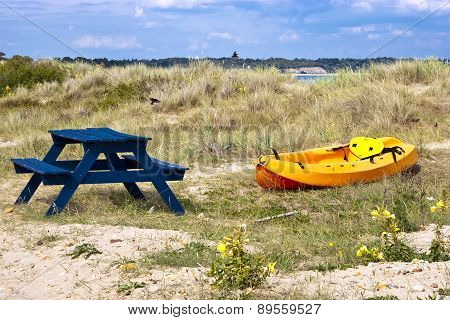 Orange and yellow kayak on a sandy dune by the sea