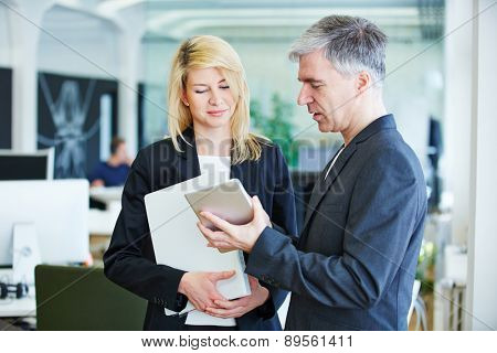 Two business people in office with tablet computer and files