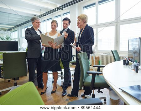 Team of business people standing with files in office