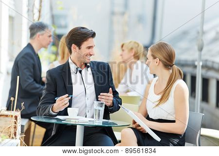 Business man and woman talking outdoors in a coffee shop with each other
