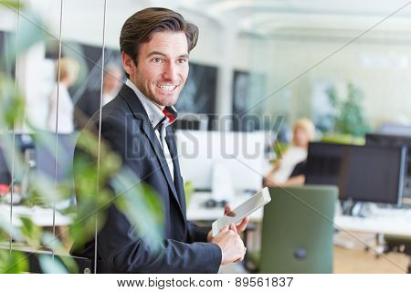 Smiling business man working with tablet PC in office