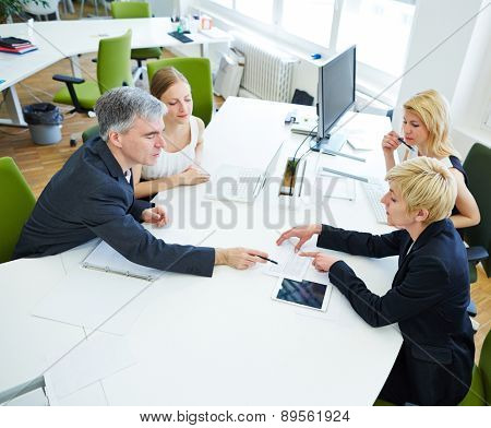 Team discussing at desk in business meeting in the office