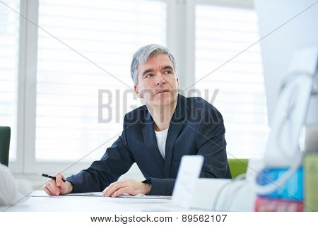 Pensive business man sitting at desk in the office