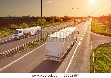 Two White Trucks On The Highway At Sunset