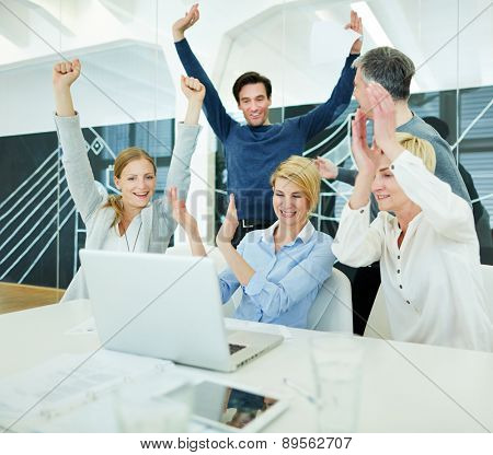 Group of happy business people cheering in office in front of computer
