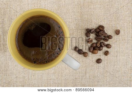 Hot Cup Of Coffee And Beans On Burlap