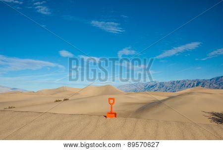 Plastic Shovel Standing In A Sand Dune